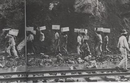 "A crew of West Indian ""Powder Men"" transporting 50 lb. boxes of dynamite on their heads."