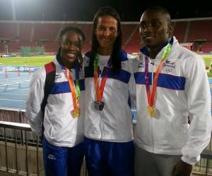 Yvette Lewis (gold), Andrea Ferris (Silver) and Alonso Edward (Gold) standing in a winning circle.  Image La Prensa.