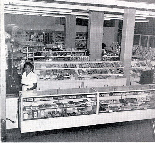 The West Indian woman behind the counter of this Balboa Clubhouse store was one of many thousands of Silver Roll mothers and wives.  Year is 1959.